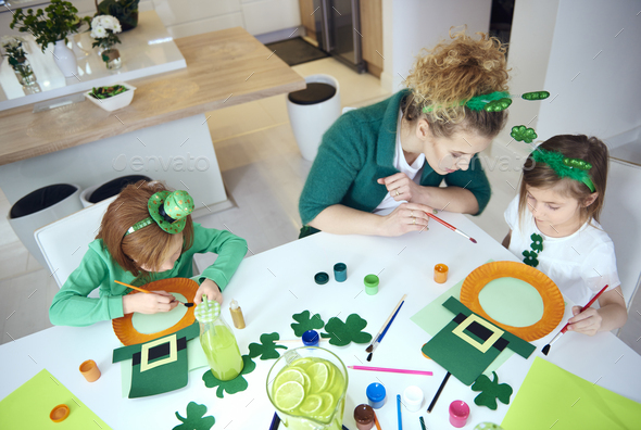 Mother with children preparing decorations for Saint Patrick's Day - Stock Photo - Images