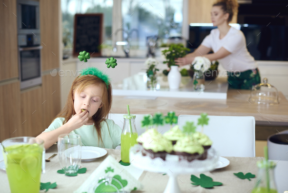Girl eating cookie at table - Stock Photo - Images
