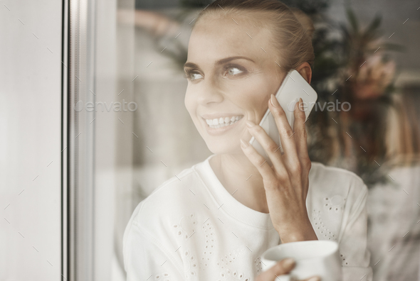 Happy businesswoman looking through window and talking by mobie phone - Stock Photo - Images