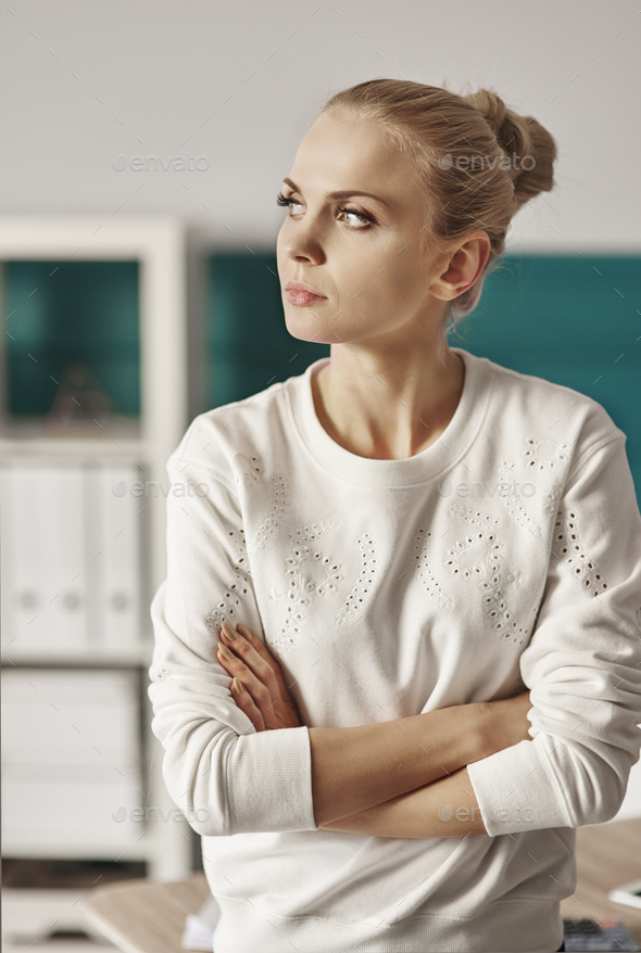 Businesswoman with arms crossed looking through window - Stock Photo - Images