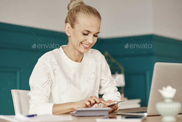Cheerful woman budgeting at home - Stock Photo - Images