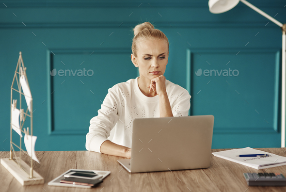 Focused and serious woman working with laptop - Stock Photo - Images