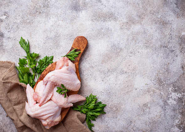 Raw chicken wings on cutting board - Stock Photo - Images