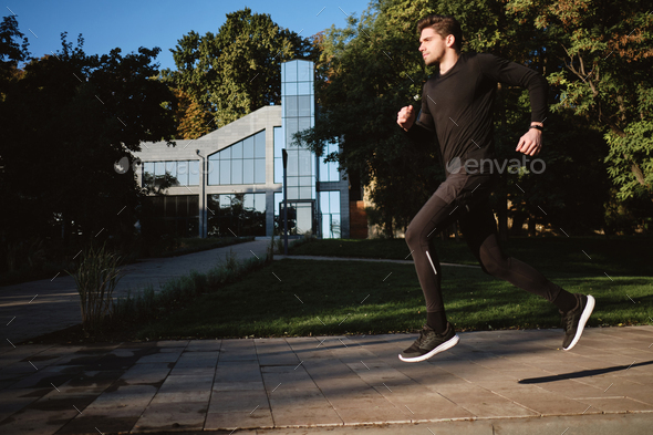 Young attractive stylish sporty man running in city park - Stock Photo - Images