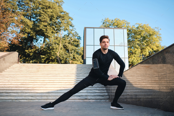 Young handsome sporty man stretching during morning workout in city park - Stock Photo - Images