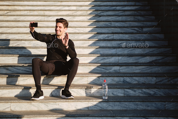 Smiling man happily showing hi gesture talking on video chat on cellphone after workout outdoor - Stock Photo - Images