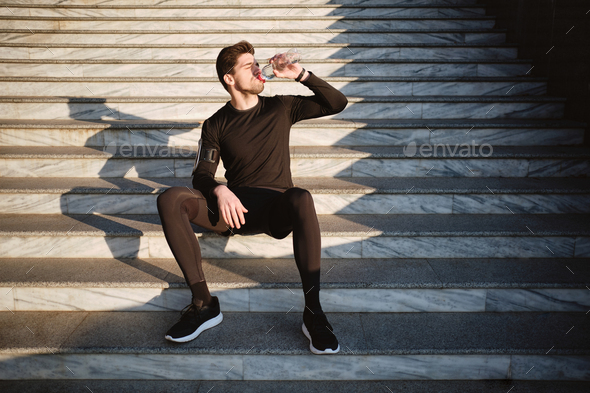 Young attractive sporty man sitting on stairs drinking water after workout outdoor - Stock Photo - Images