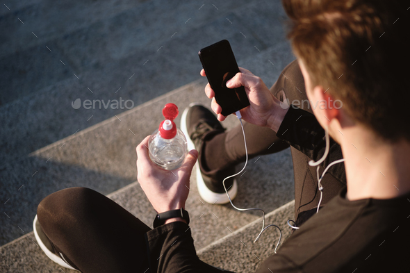 Close up of sporty man with bottle of water using cellphone outdoor - Stock Photo - Images