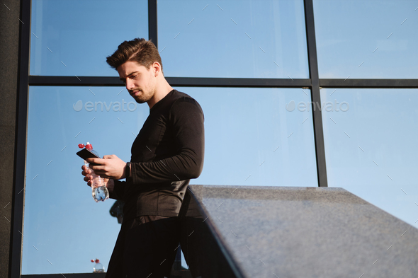 Young confident sporty man with bottle of water using cellphone after workout outdoor - Stock Photo - Images