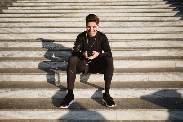 Handsome smiling sporty man sitting on stairs joyfully using cellphone after workout outdoor - Stock Photo - Images