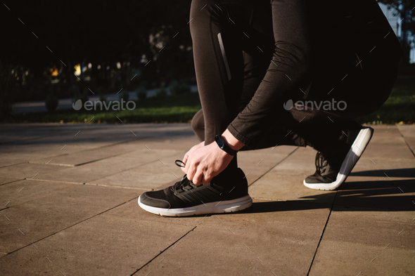 Close up sporty man tying shoelaces on sneakers during morning run in city park - Stock Photo - Images