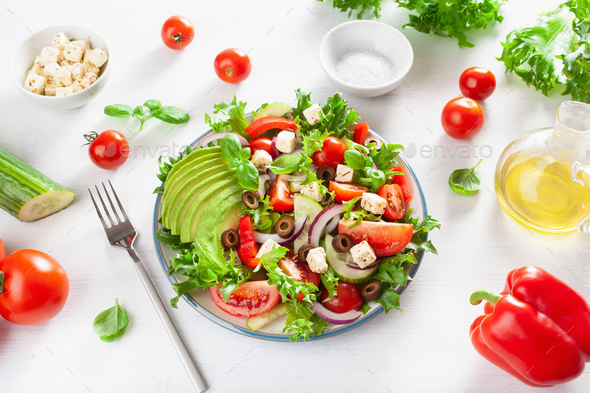 greek style avocado tomato salad with feta cheese, olives, cucum - Stock Photo - Images