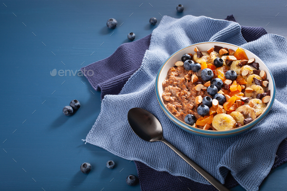 chocolate oatmeal porridge with blueberry, nuts, banana, dried a - Stock Photo - Images