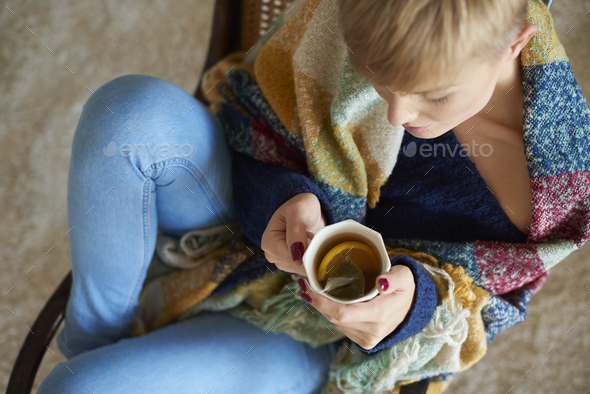 Young woman wrapped in a blanket drinking hot tea with lemon - Stock Photo - Images