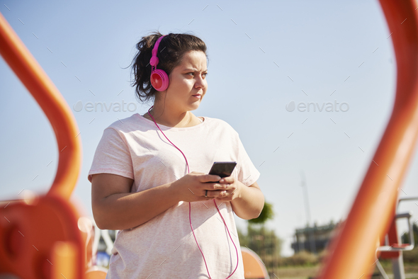 Woman choosing playlist for exercising - Stock Photo - Images