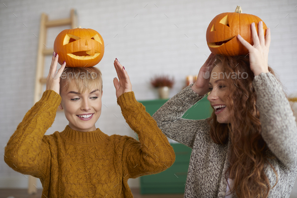 Girls having fun with halloween pumpkins - Stock Photo - Images