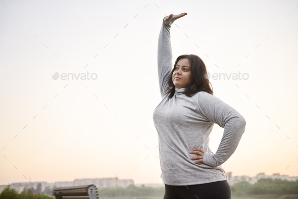 Young woman stretching before running - Stock Photo - Images