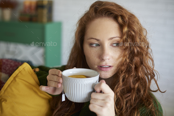 Young woman drinking tea with lemon in the living room - Stock Photo - Images
