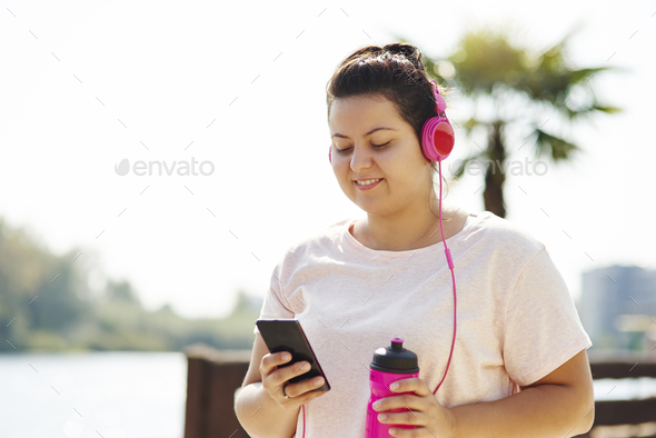 Woman choosing playlist for morning running - Stock Photo - Images