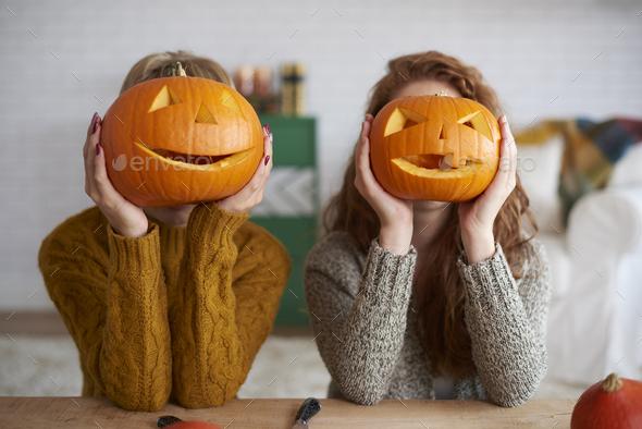 Two women showing halloween pumpkins - Stock Photo - Images