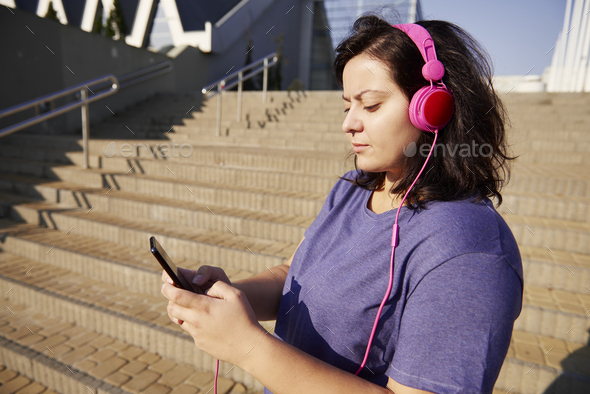 Woman choosing perfect playlist for morning running - Stock Photo - Images