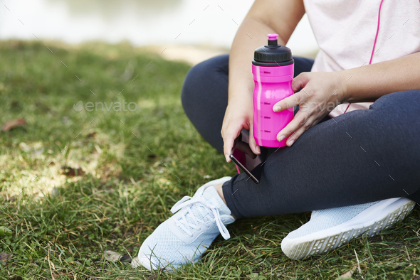 Tired woman drinking water after hard workout - Stock Photo - Images