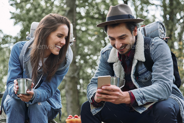 Happy backpackers drinking coffee and using mobile phone - Stock Photo - Images