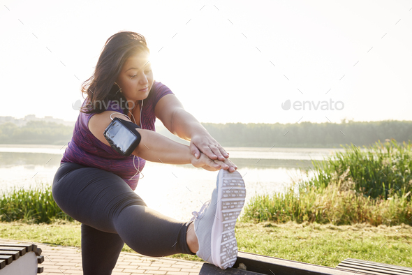Young woman stretching her legs before running - Stock Photo - Images
