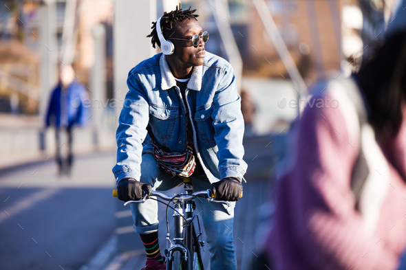 Handsome young man riding bike in the street. - Stock Photo - Images