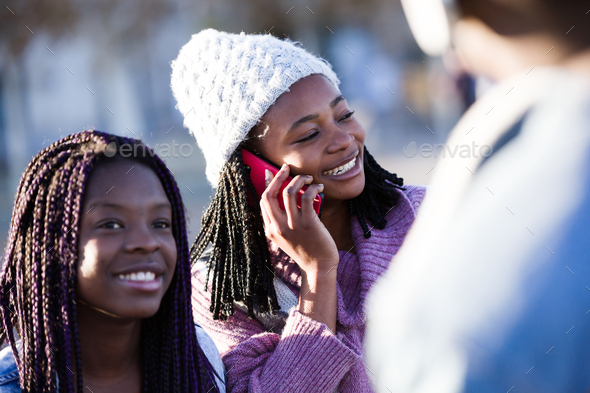 Beautiful young woman using her mobile phone in the street. - Stock Photo - Images