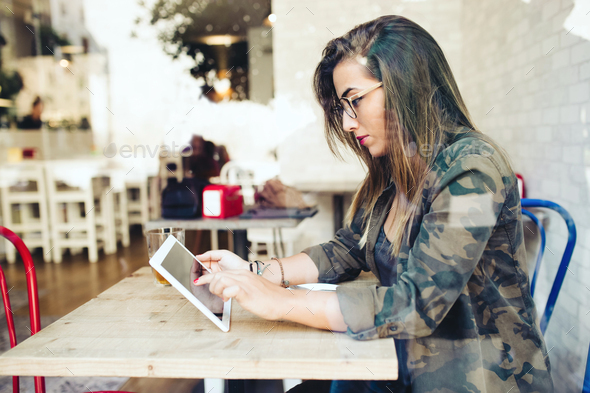 Beautiful young woman using her digital tablet in cafe. - Stock Photo - Images