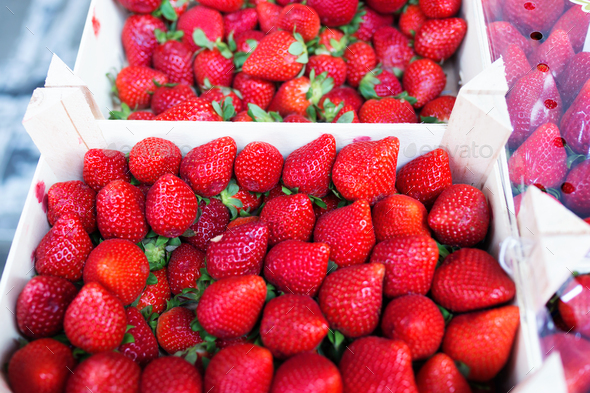Colorful strawberries trays in health grocery shop. - Stock Photo - Images