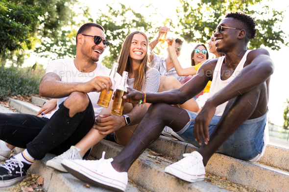 Group of young people toasting with beer in an urban area. - Stock Photo - Images
