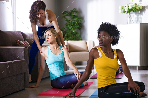 Pretty yoga instructor helping her student in a yoga session at - Stock Photo - Images