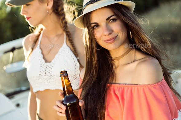 Beautiful young women drinking beer and enjoying summer day. - Stock Photo - Images