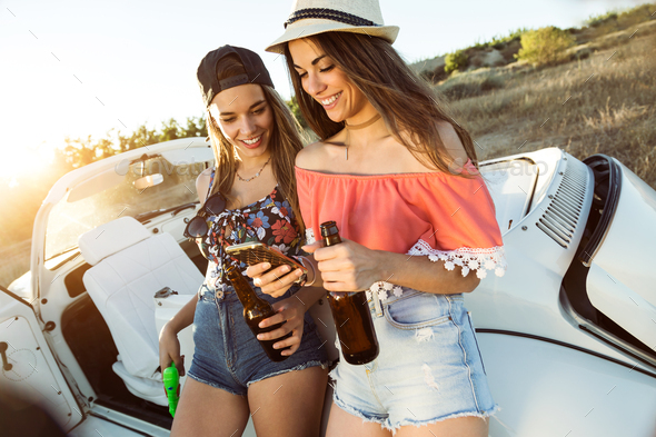 Two beautiful young women using mobile phone on road trip. - Stock Photo - Images