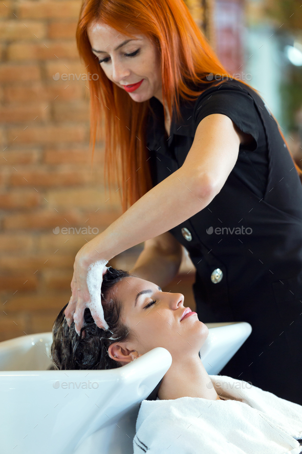 Beautiful young woman washes hair in a beauty salon. - Stock Photo - Images