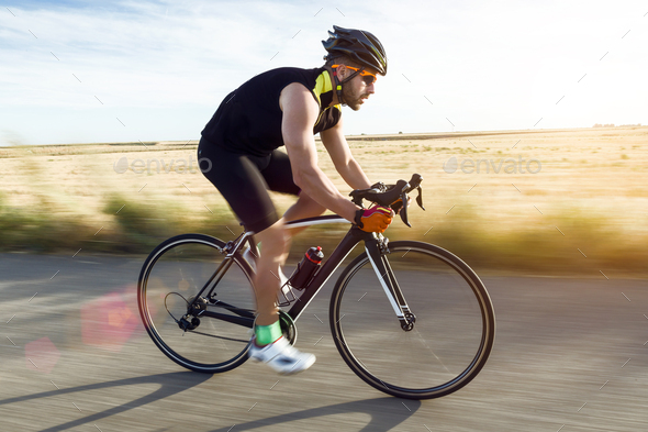 Handsome young man cycling on the road. - Stock Photo - Images