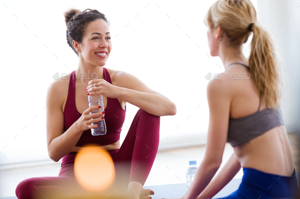 Two pretty young sporty women relaxing after yoga session at hom - Stock Photo - Images