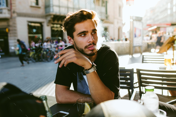 Handsome young man smoking in the street. - Stock Photo - Images