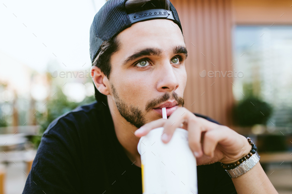 Handsome young man drinking refreshment at outdoor bar. - Stock Photo - Images