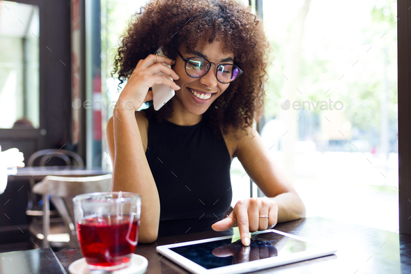 Beautiful young woman using her mobile phone in cafe. - Stock Photo - Images