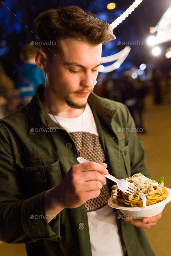 Handsome young man eating chips in the street. - Stock Photo - Images