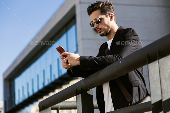 Handsome young man using his mobile phone in the street. - Stock Photo - Images