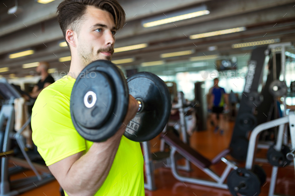 Handsome young man doing muscular exercise in gym. - Stock Photo - Images