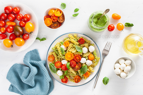 healthy fusilli pasta with pesto sauce, roasted tomatoes, mozzar - Stock Photo - Images