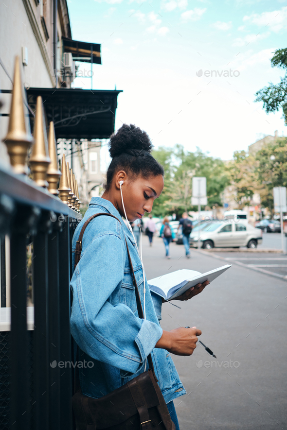 Сasual African American student girl in denim jacket with notepad studying on city street - Stock Photo - Images
