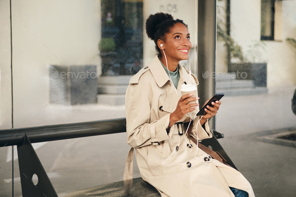 Beautiful African American girl in stylish trench coat happily listening music at bus stop - Stock Photo - Images