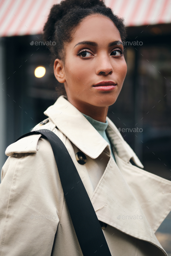 Portrait of beautiful African American casual girl in trench coat thoughtfully looking away outdoor - Stock Photo - Images