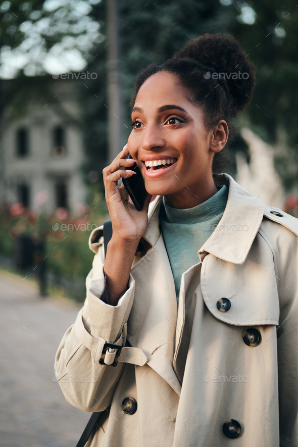 Pretty emotional stylish African American girl in trench coat happily talking on cellphone outdoor - Stock Photo - Images
